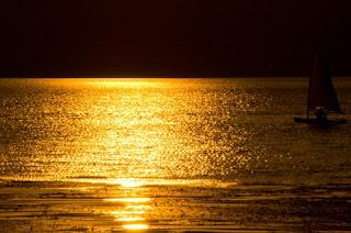 海に映る金色の夕日の光、そしてヨット