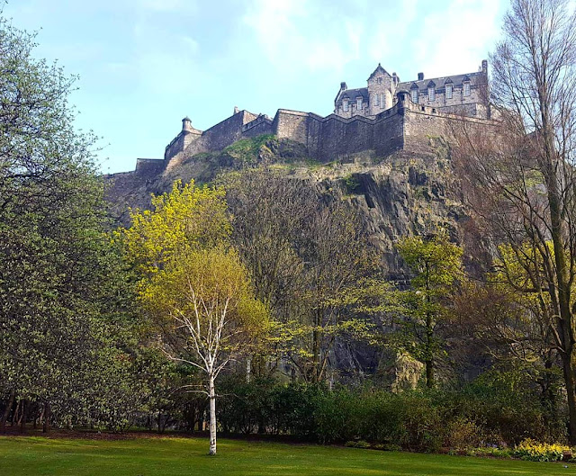 Edinburgh Castle sits atop a rocky hill. Below, the green trees and flowers of Princes Street Gardens contrast with the imposing stone.
