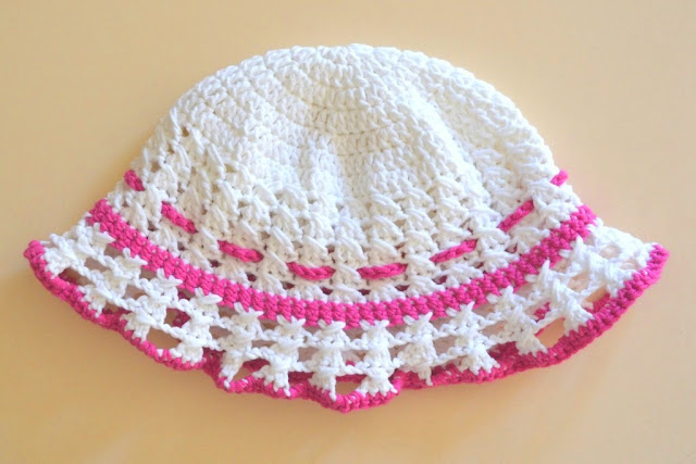 A white hat is laid out flat with pink trim along the brim edge and where the brim meets the body of the hat,  The top line of pink is a pink drawstring, the ends of which tie up at the back to adjust the circumference.