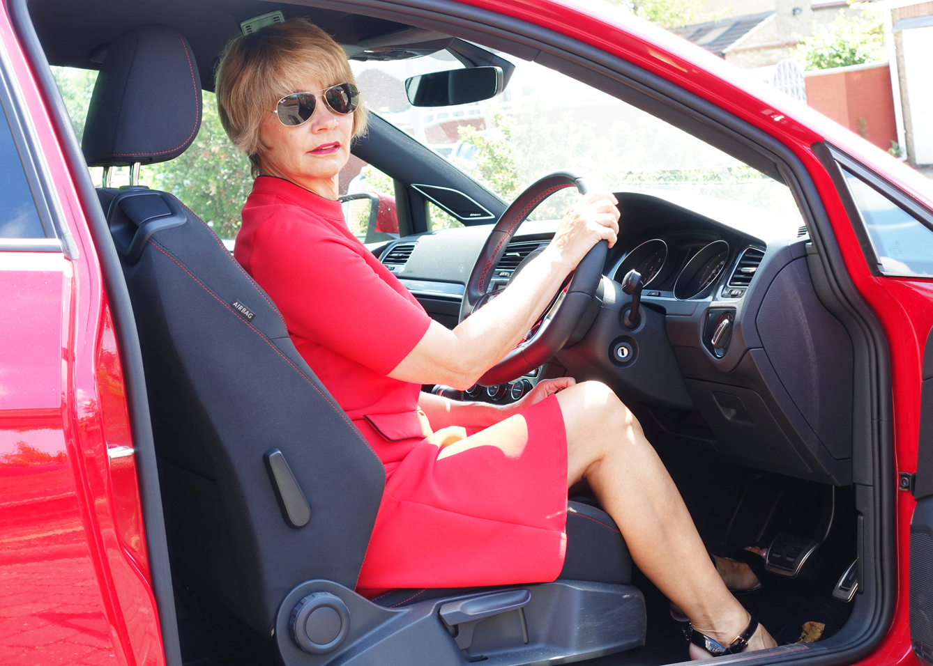 Gail Hanlon from Is This Mutton? in red skater dress and red Golf car in an article on chic, quirky dresses for the workplace