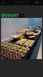 На столе приготовлены закуски и бутерброды к фуршету в большом количестве