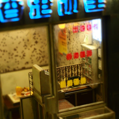 Exterior of a miniature Hong Kong cafe at night.
