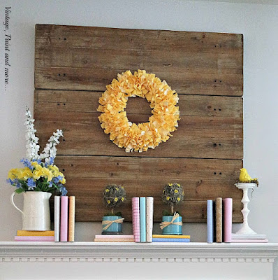 a spring mantel done with a yellow rag wreath, books covered with pastel scrapbook papers and flowers in ironstone pitchers