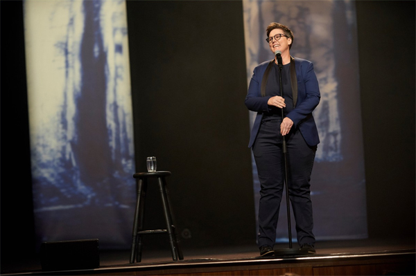 image of Hannah Gadsby, a fat white butch lesbian woman with short-cropped dark hair, standing on stage wearing a blue blazer with a dark shirt and dark slacks