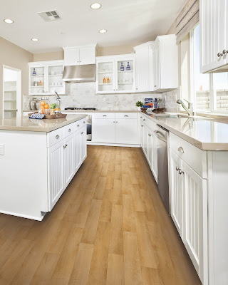 A lighter finish on this hardwood floor matches the bright kitchen design.