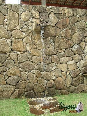 Tipo de muro de pedra com pedra bruta com a ducha d'água na bica de pedra com o piso de pedra em baixo da ducha com os pedregulhos do rio e o gramado de grama esmeralda.