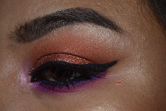 A picture of a Orange and Fucsia makeup look using Huda Beauty