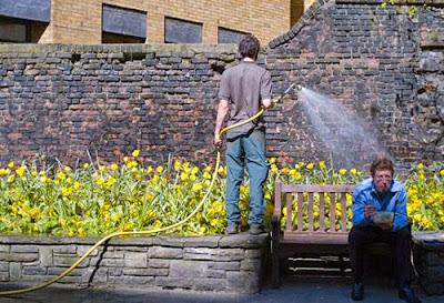 Jardineiro molhando as plantas e parece que está regando um homem sentado num banco