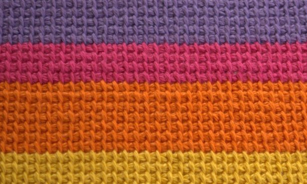 Crocheted 'afghan stitch' also known as tricot or Tunisian simple stitch in horizontal bands of colour from top to bottom: purple, pink, orange and yellow. The stitch creates a square grid pattern.