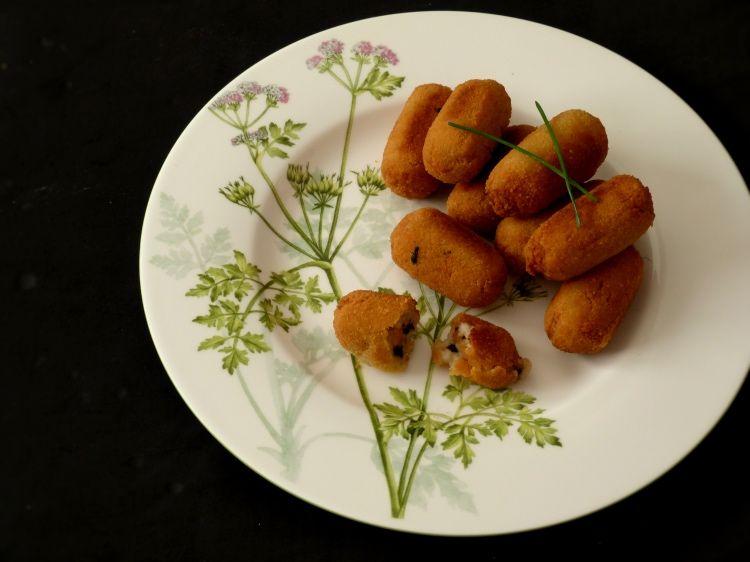 plato con croquetas de pollo y ajo negro decordas con ramas de cebollino