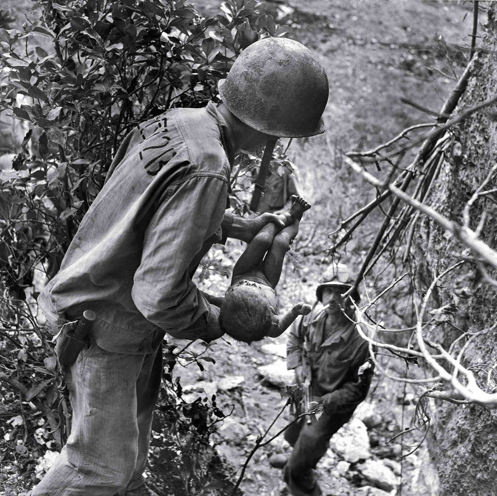 American Marine cradling tiny infant's barely living body which was found face down in a cave where native islanders had been hiding to escape the fighting between US and Japanese forces.