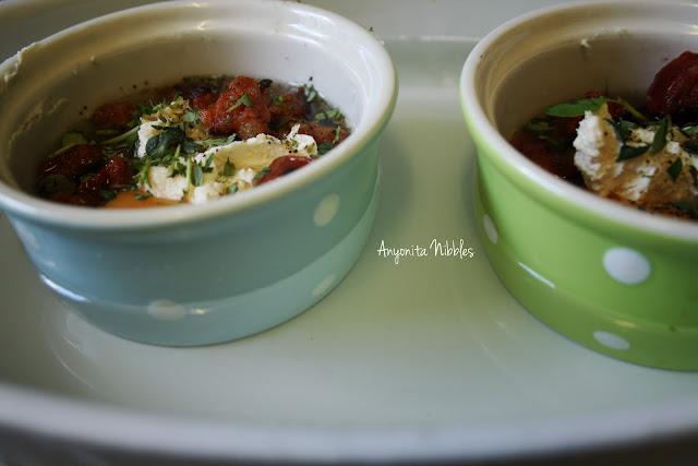 Two rammekins of ouefs en cocotte avec chorizo et mascarpone in a bain marie