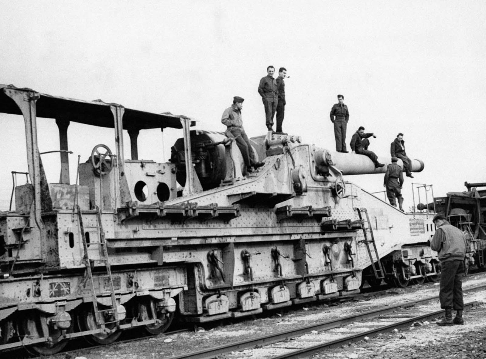 American soldiers pose on a captured German railway gun. 1940.