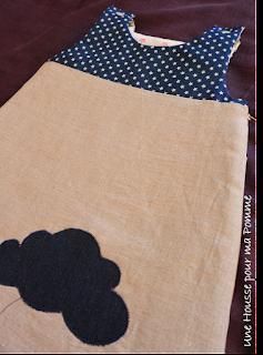 """Turbulette naissance (longueur 70 cm) sur le thème Du rêve sur un nuage en lin coloris naturel et coton bleu brut étoiles écrus sur l'extérieur, coton intérieur écru étoiles rouges, appliqués nuage en jeans brut et écriture ''dream"""", fermeture éclair beige sur le coté, pressions écrues épaules, doublée en ouatine pour les nuits fraiches, taille 0-3 mois."""