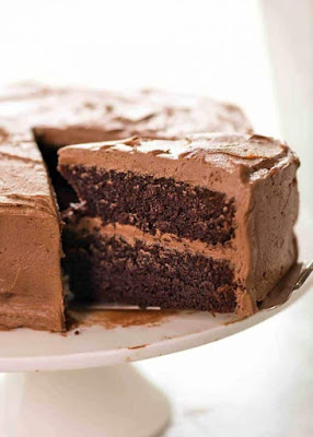 A photo showing half a Chocolate Cake frosted with Chocolate Buttercream on a white cake stand with a large slice partially pulled out