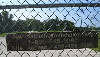 Chain link fence with parking lot visible through it, and sign giving the Malcolm X Foundation web address