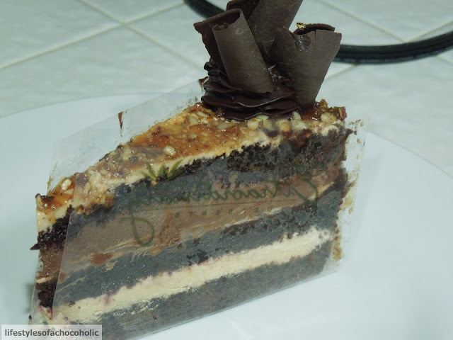 slice of layered chocolatey cake on a white plate from extraordinary desserts