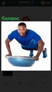 Мужчина отжимается двумя руками,сохраняя баланс