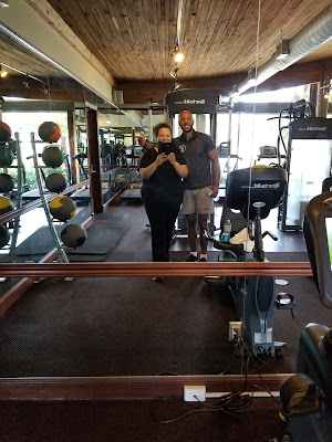 Tim and his mom posing in the mirror at the gym
