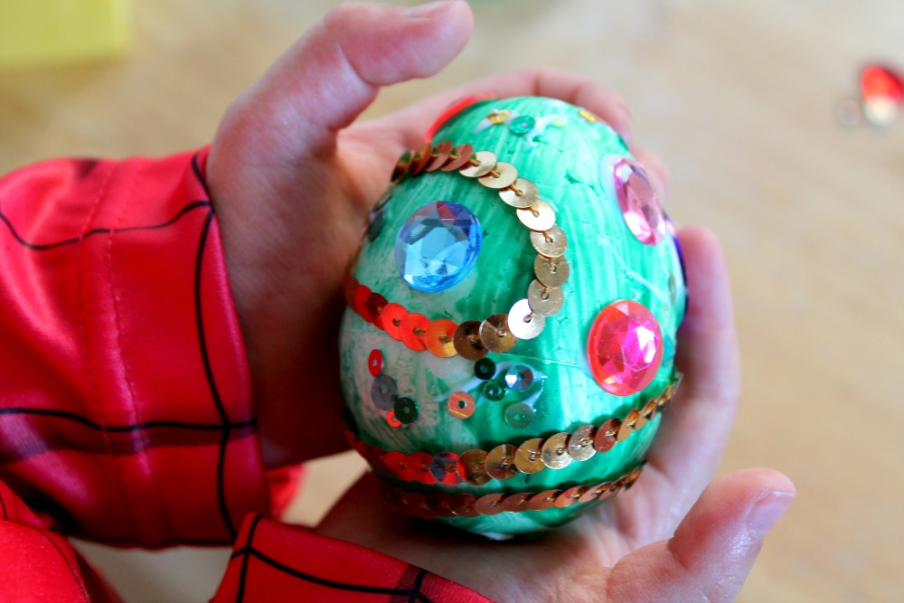 child-holding-decorated-craft-egg