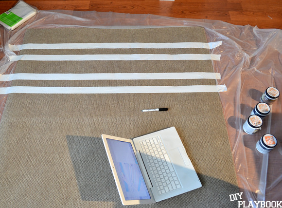 Duct tape stripes in varying sizes create a fun pattern for our DIY outdoor rug.