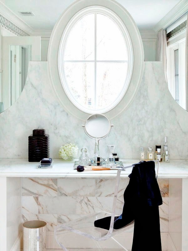 Vanity in a girly bathroom under an oval window with marble floor and a lucite chair