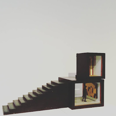 Assemblage art piece by Alex Asch, with two black boxes and a staircase.