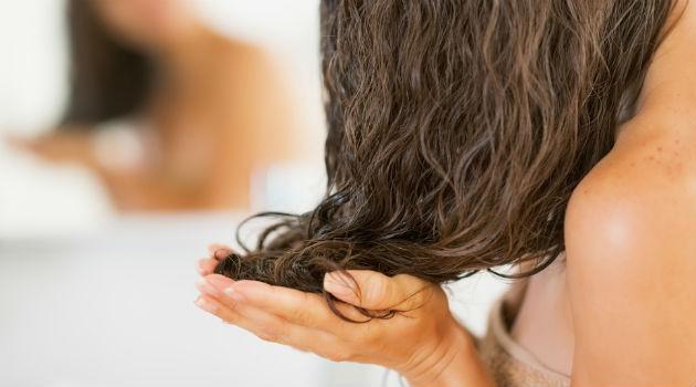 Para conseguir deixar os cachos definidos, o primeiro passo é tirar o excesso de água do cabelo com a mão e secá-lo com um papel toalha. Isso livra os cachos do frizz.