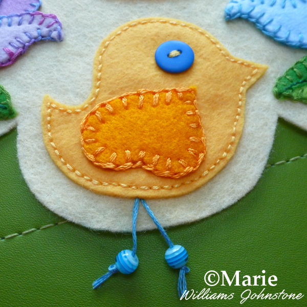 Blue beads on embroidery floss add detail to this hand sewn felt bird