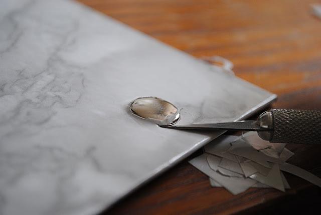 De randjes plakplastic rondom de drukknop wordt met een klein mesje voorzichtig bijgewerkt.