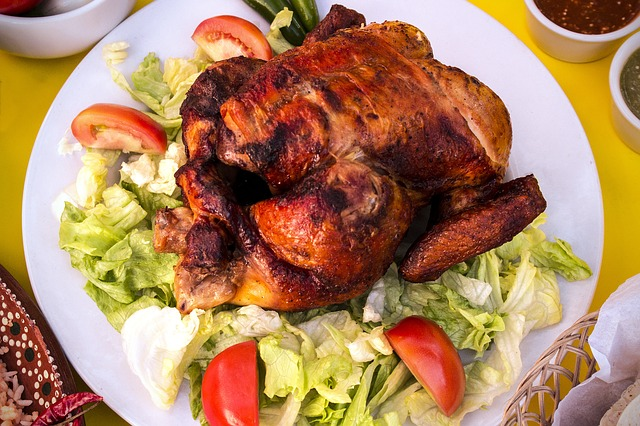 Rotisseries Chicken Sitting on a Bed of Lettuce with Tomatoes