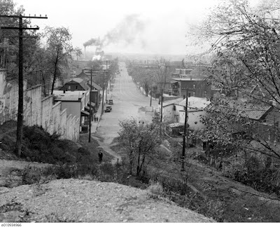 Black and white photo looking from the top of Nanny Goat Hill at the west end of Laurier (where the Slater ramp up to Bronson is now) down the hill and west along Albert and Wellington Street. At the foot of the viewer is a hill with various shrubs and a man walking up a narrow footpath through it. To the left is a concrete retaining wall with stepped panels following the hill. At the bottom of the hill is a stub of a street with buildings and two parked cars and a sidewalk on the left (south) side, beyond which Albert Street, bearing two sets of streetcar tracks, swoops in from the right and goes off straight away from the viewer. On either side of Albert Street is a sidewalk separated from the roadway by a boulevard, the one on the left planted with utility poles and the one on the right planted with trees. In the distance at the end of Albert Street is the silhouette of the railroad roundhouse, and to the left of it are smokestacks from various industrial facilities (including at least one brewery). I'm told this photo is from 1938 based on the presence and absence of various buildings in the background but the cars are all of an older vintage than other photos known to be from that year.