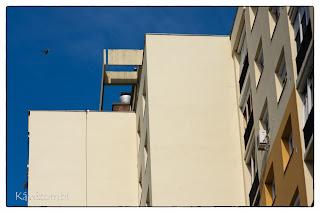 Sárga falú panelház Szegeden repülő galambbal