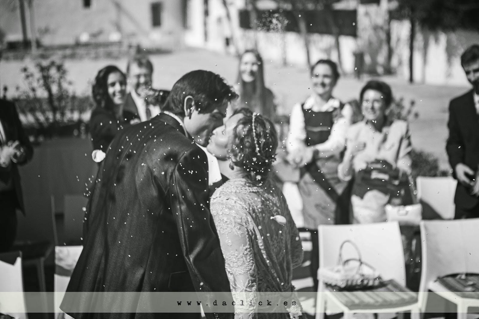 novios se besan mientras los invitados les tiran arroz