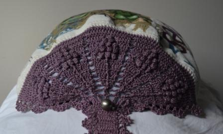 The semi-circular top design has been draped over a cushion to spread out the design. Viewed from the top, five grape motifs fan out from the central button with filet crochet gaps between each one.