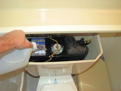 Pouring water into the toilet tank around the Flushmate unit.