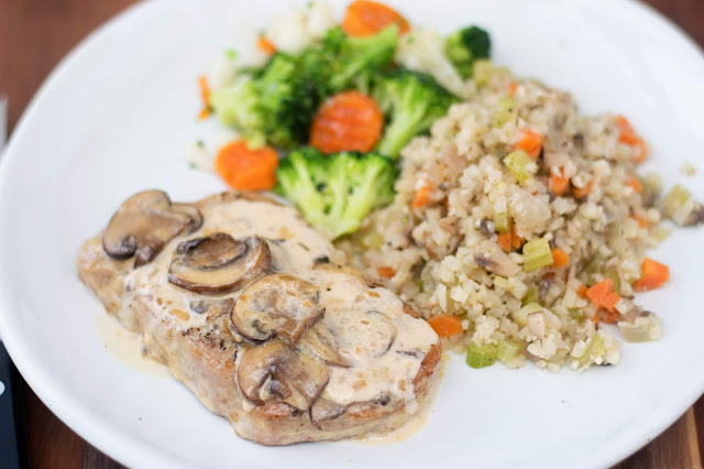 A white plate with one of the pork chops smothered in the sauce with a side of cauliflower rice and steamed vegetables.
