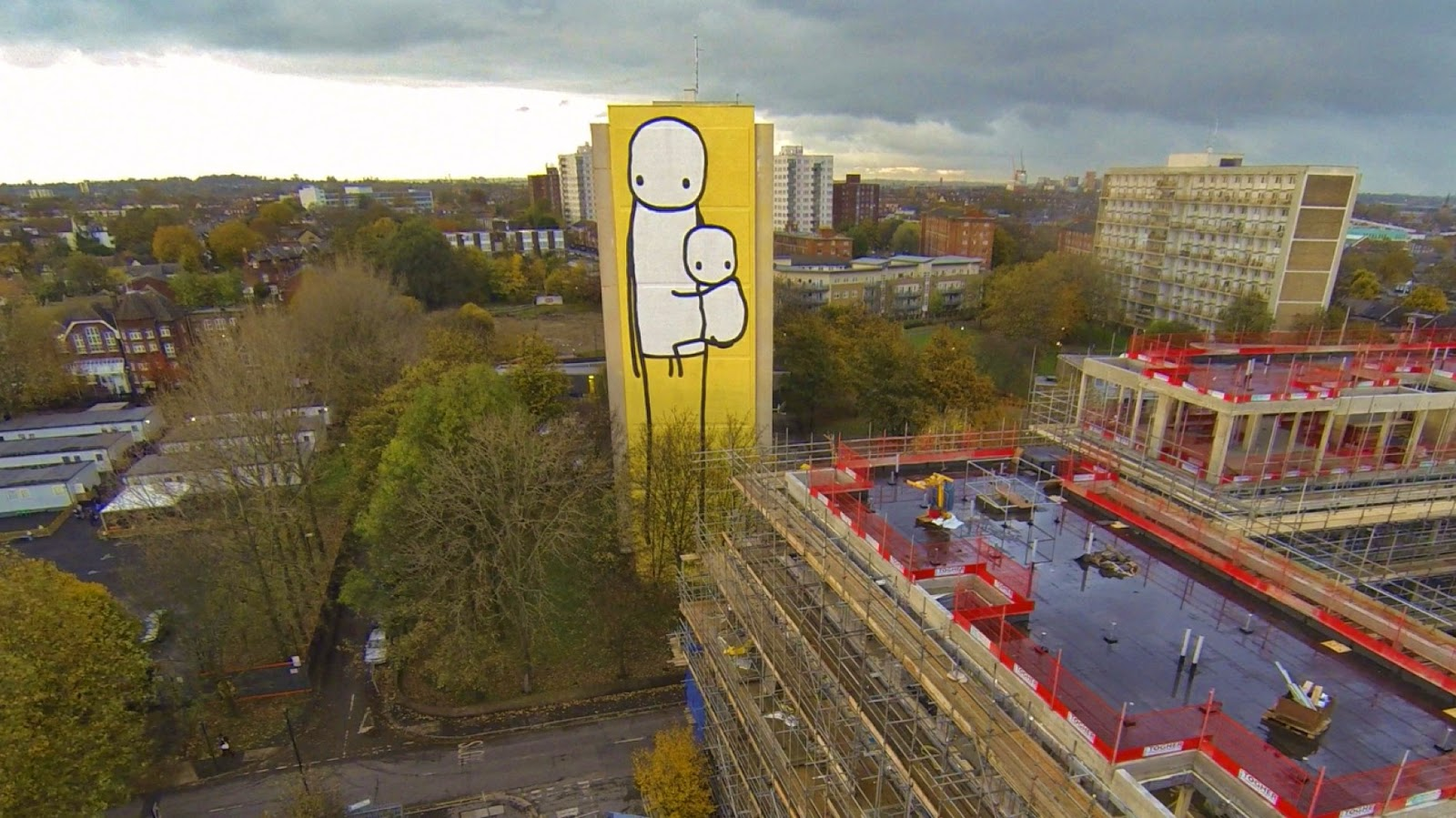 A newly completed 125 ft high mural painted by Stik on a condemned council owned tower block in Acton, West London is the tallest street artwork in the UK. The artwork depicts a mother and child looking forlornly from their condemned council block at the luxury apartment complexes being built around them.