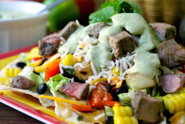 A fresh, healthy and delicious Taco Salad topped with Cilantro Lime Rice, grilled veggies and sirloin steak.