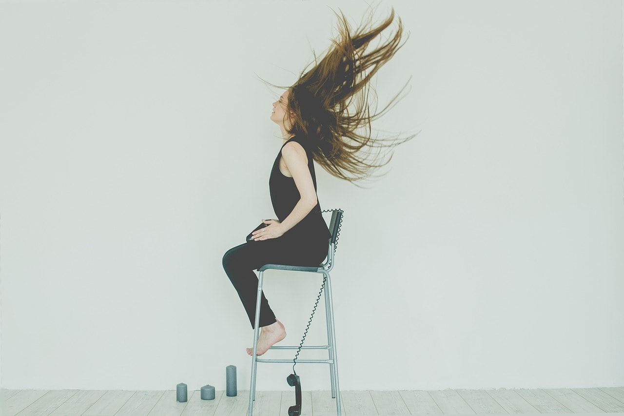 Mujer en silla con teléfono arrojado