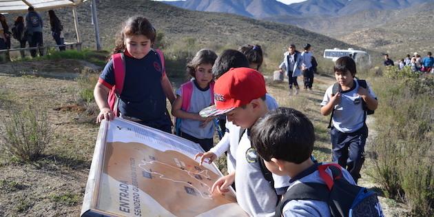 Niños observan panel turístico