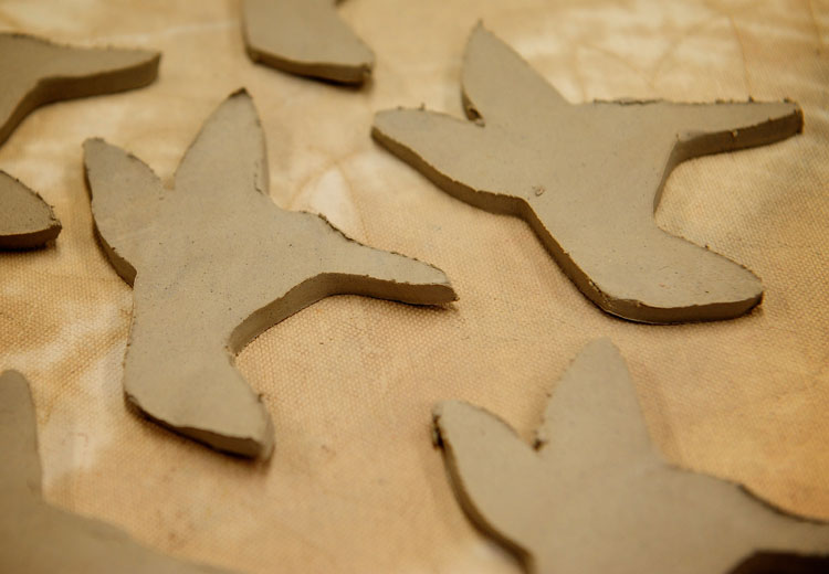 Smooth out the rough edges of the clay cut-outs with a sponge.