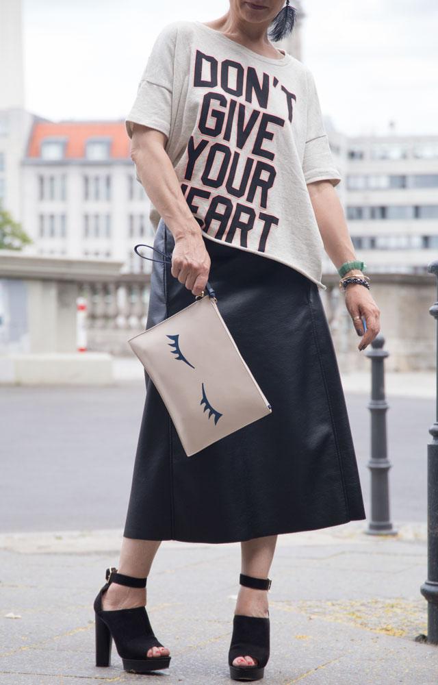 Outfit, langer Lederrock mit High Heels und Sweater, Clutch mit Augen