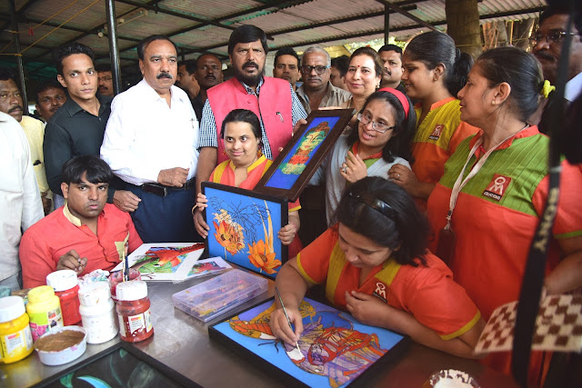 Shri Ramdas Athawale posses with paintings created by specially-abled women