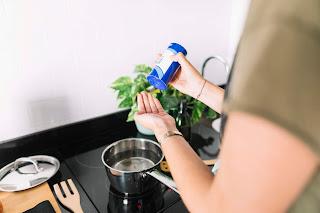 Mujer poniendo sal en la mano mientras prepara la comida sobre la estufa de inducción.