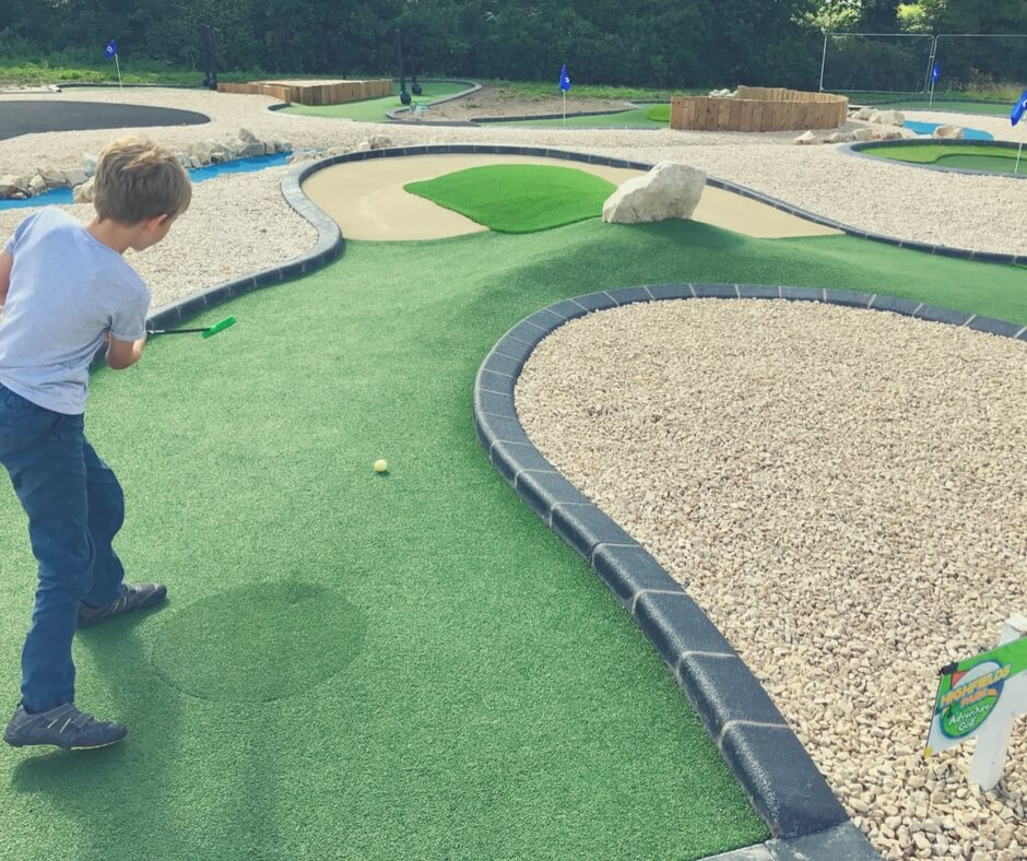 Little boy tries to hit golf ball over mound in adventure golf