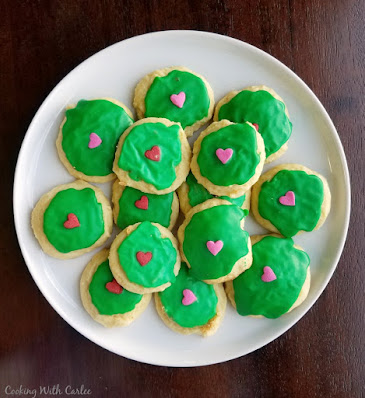sour cream cookies topped with green icing and a large heart sprinkle to mimic the Grinch
