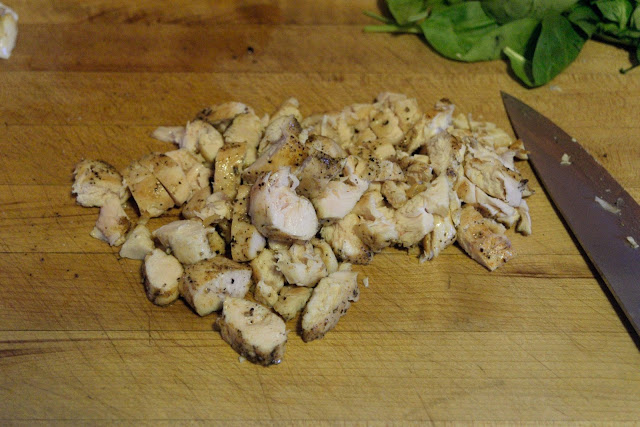 The cooked chicken being cut into a dice on the cutting board.