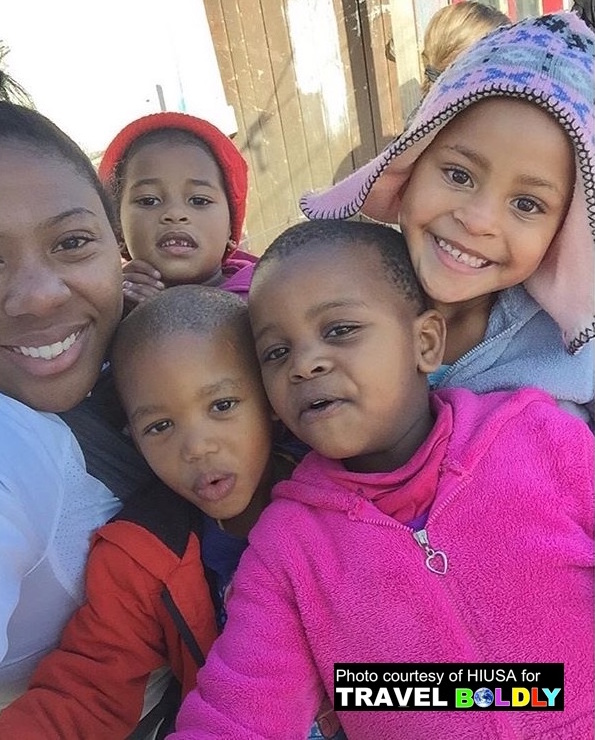 Tianna, (left) one of the 2016 Explore the World Travel Scholarships is surrounded by children during her  visit to Capte Town, South Africa. HIUSA for Travel Boldly