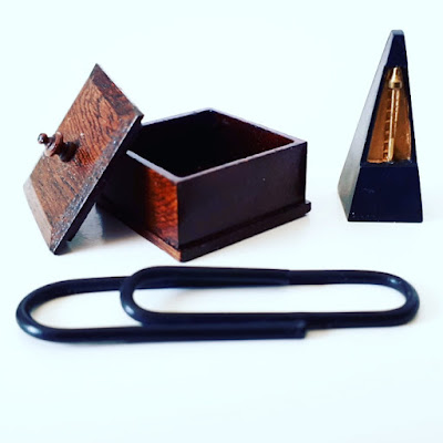 Full-sized paper clip with a one-twelfth scale miniature wooden box and a metronome next to it